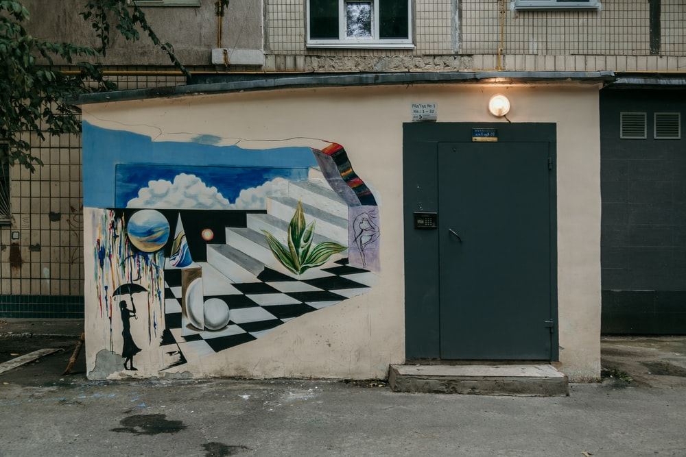 white building with closed black door and wall with graffiti