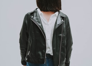 person wears black leather zip-up jacket close-up photography