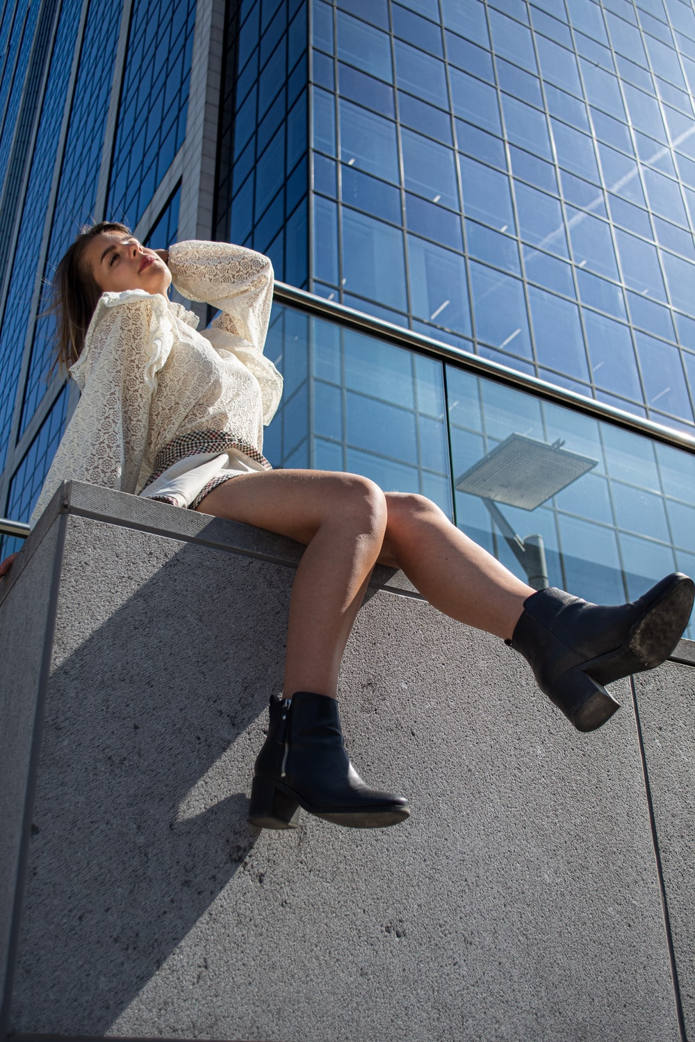 woman sitting beside concrete building during daytime close-up photography
