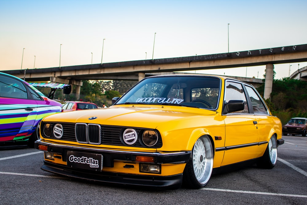 yellow BMW New Six coupe parking near road