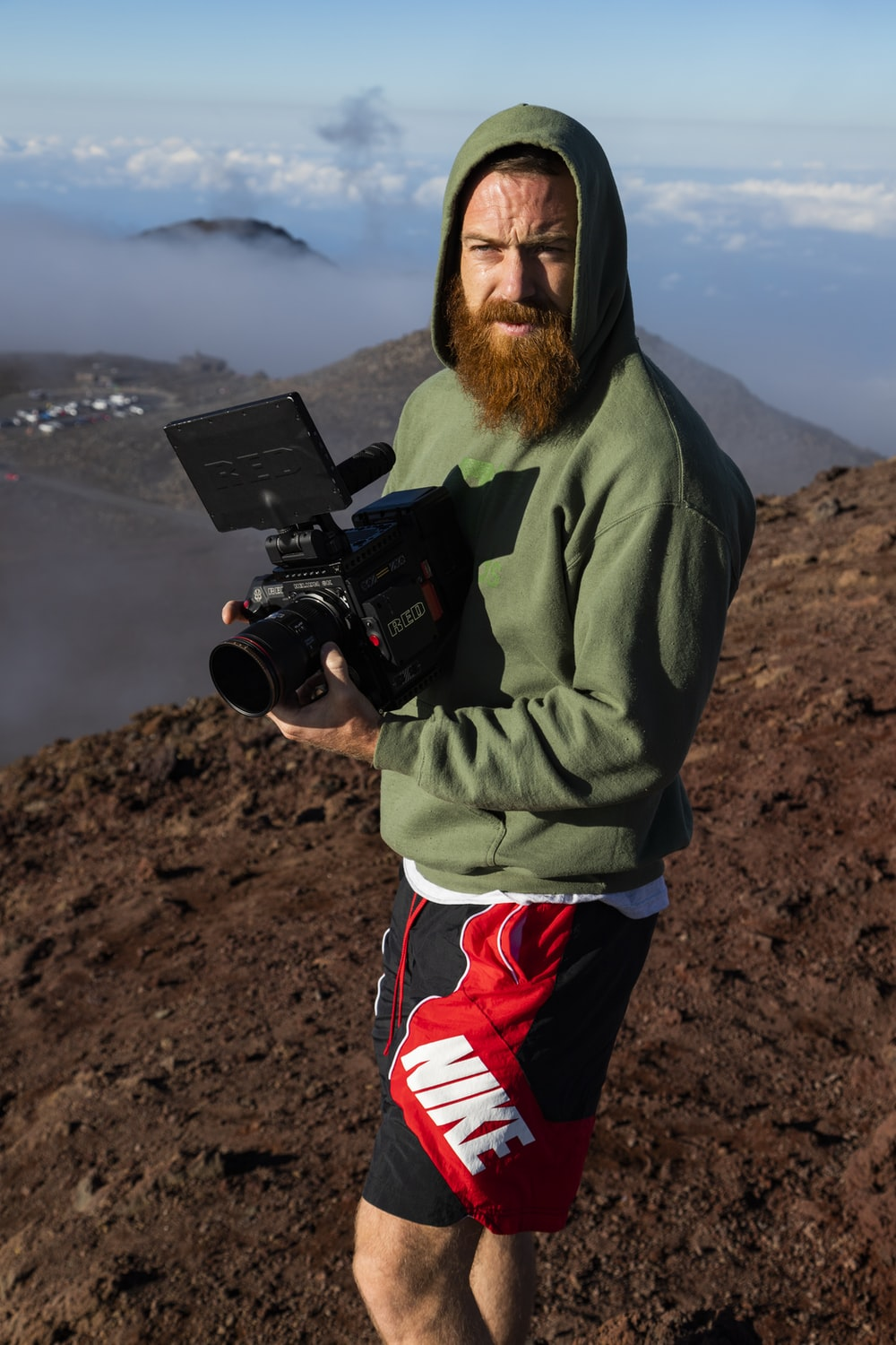 man standing on top of mountain while holding video camera