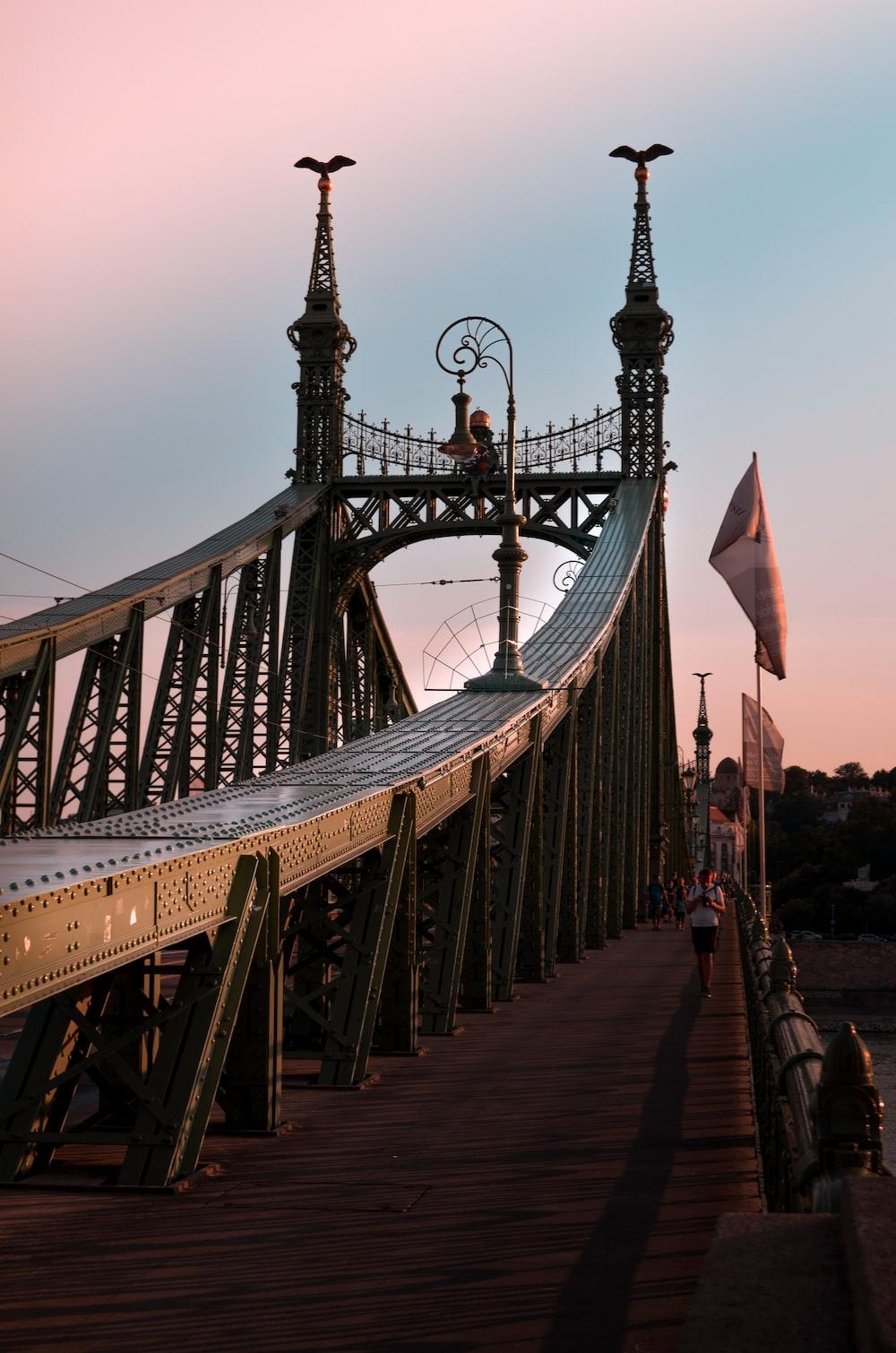 man walking on metal bridge