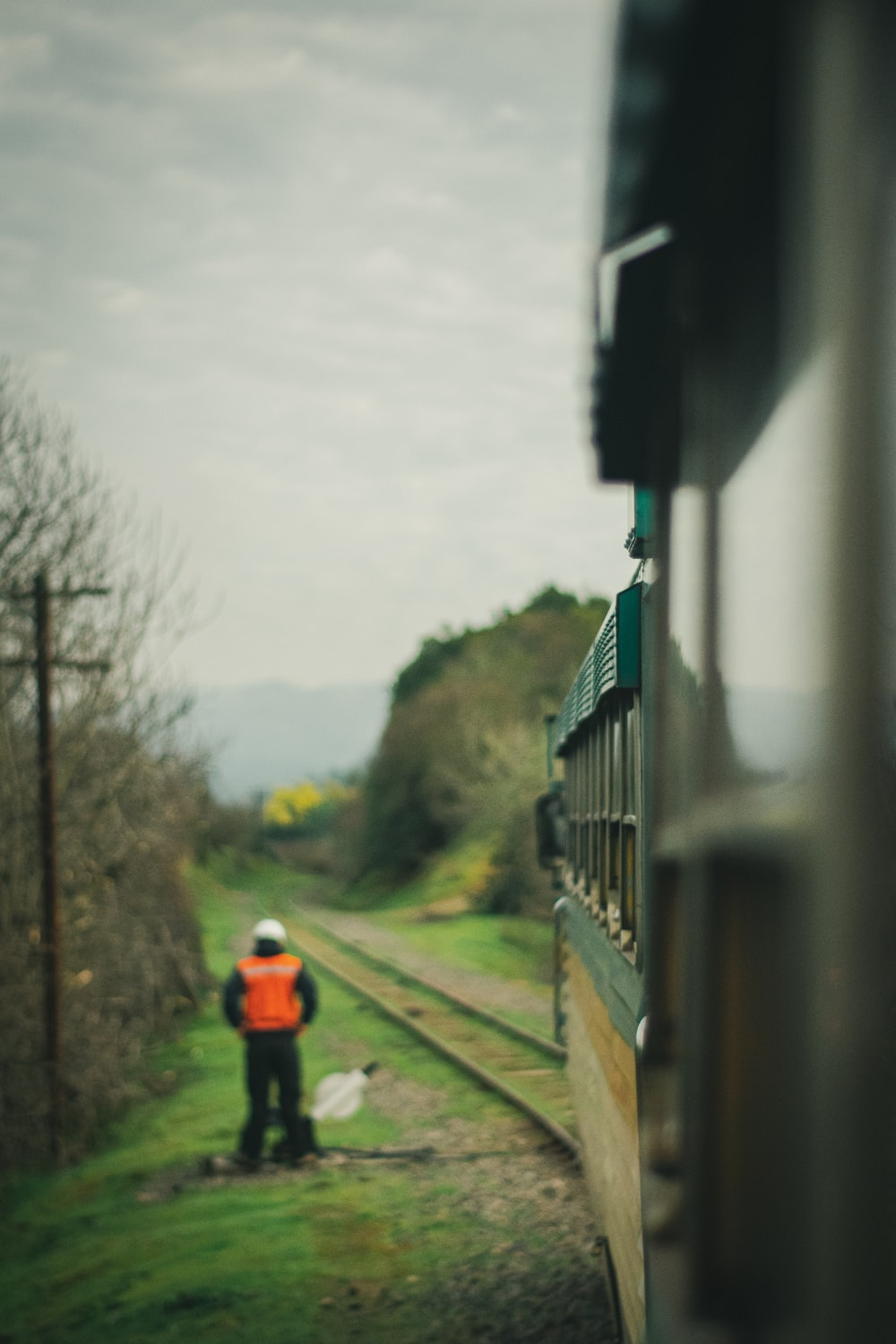 person standing beside train rail near train during daytime