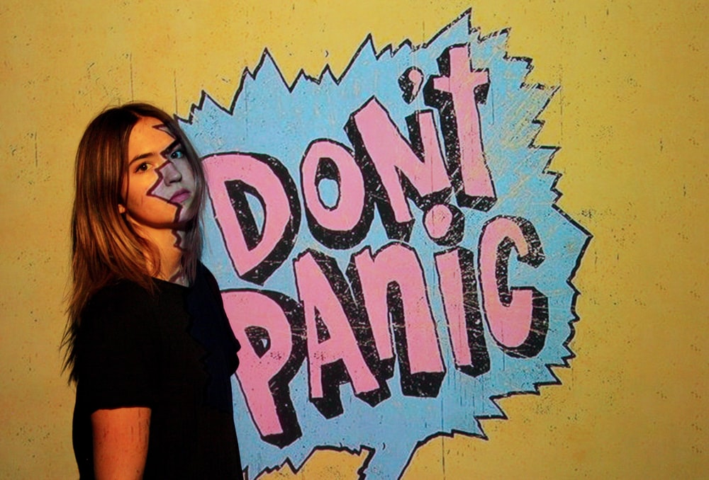 woman wearing black crew-neck t-shirt with don't panic background
