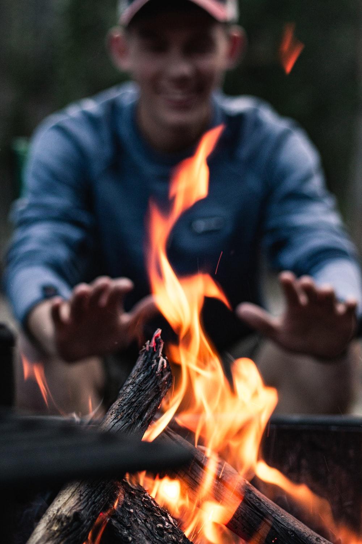 man sitting beside bon fire during daytime