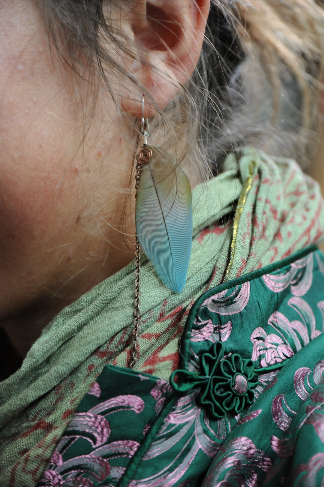 Leaf earring, metal chain detail, light green and red Indian fabric, gold metallic edging, forest green and pink silk jacket, green daisy button, blonde hair, a Buddhist student's style, In Celebration Centennial, Dilgo Khyentse Yangsi Rinpoche, Vancouver B.C, Canada