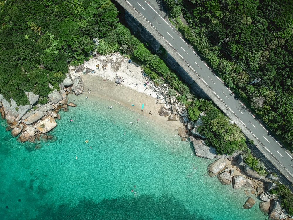 aerial photography of road beside body of water during daytime