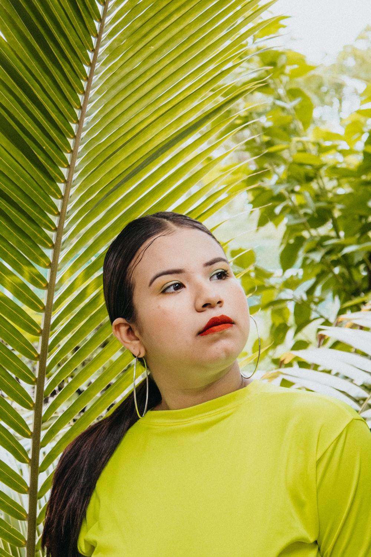 woman standing near palm leaf