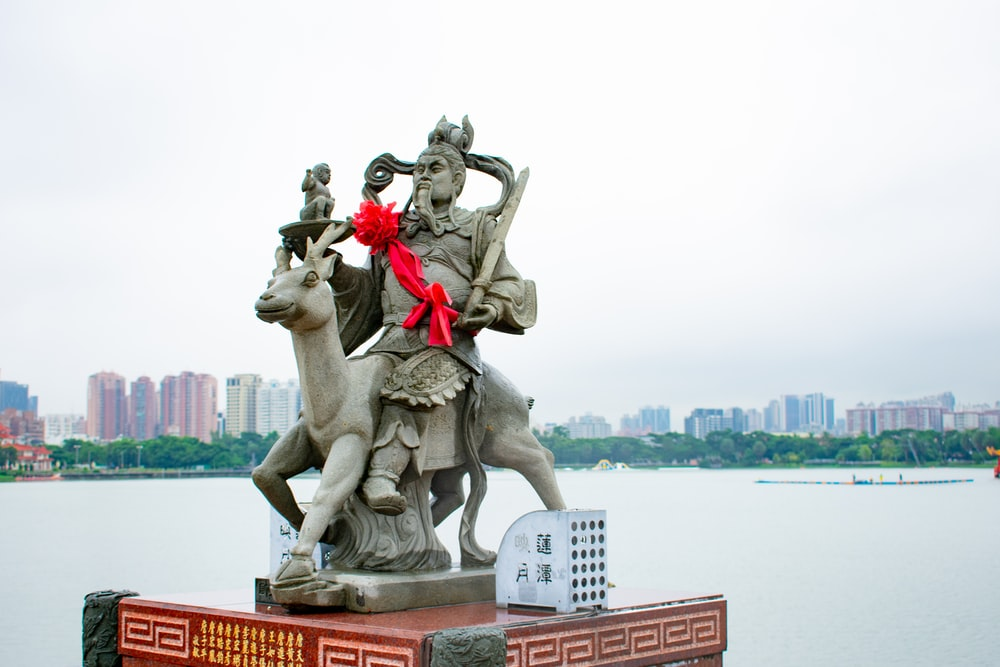 man riding on animal statue