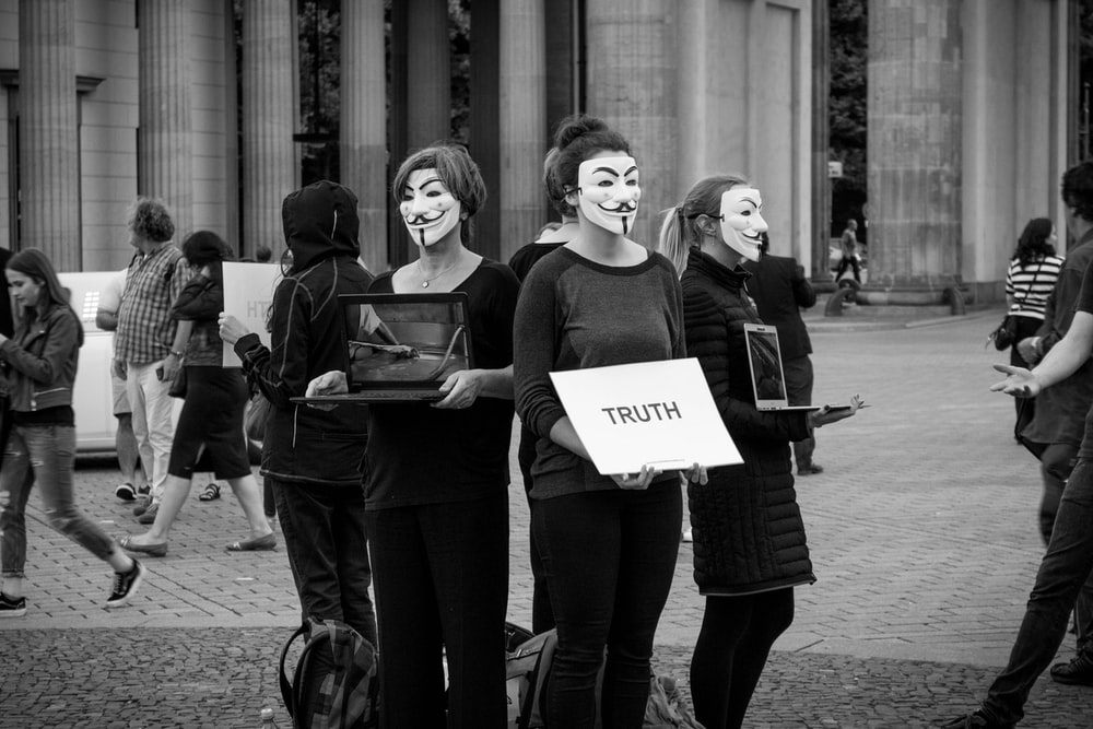 people with mask with truth poster