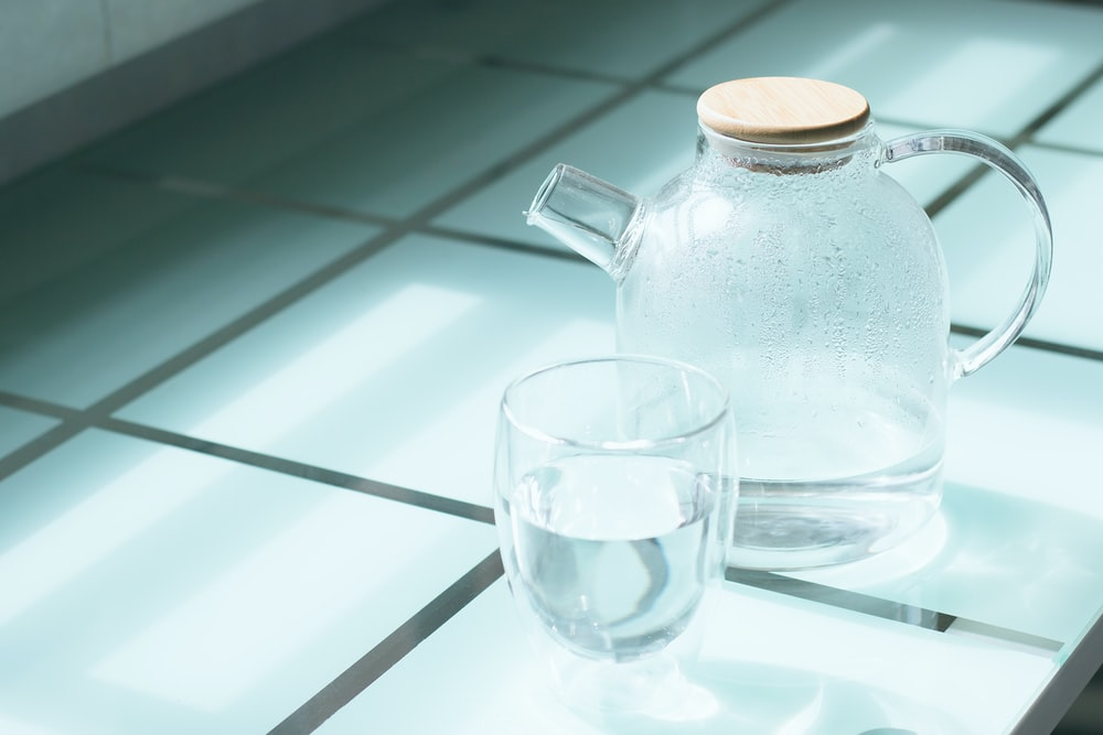 half-filled clear glass cup beside pitcher