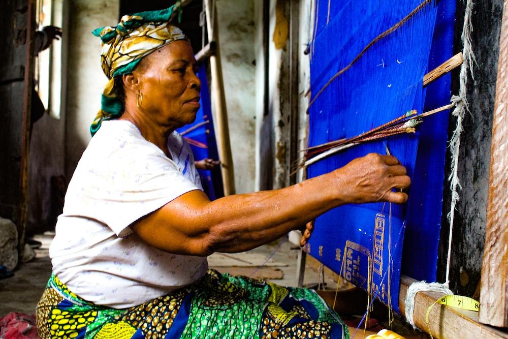 woman sitting beside blue wall