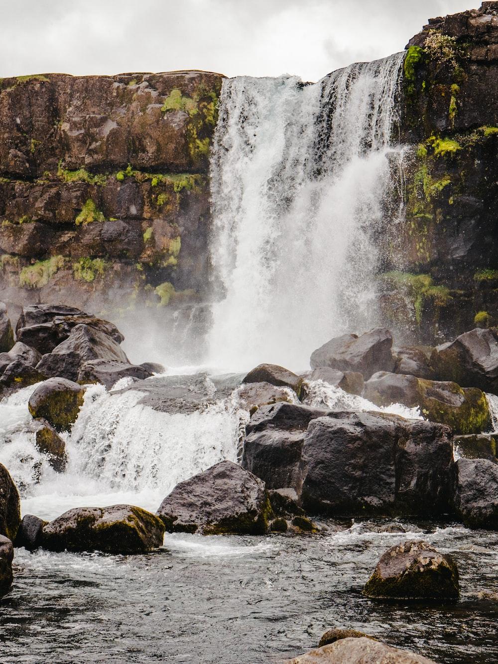 waterfall under gray sky