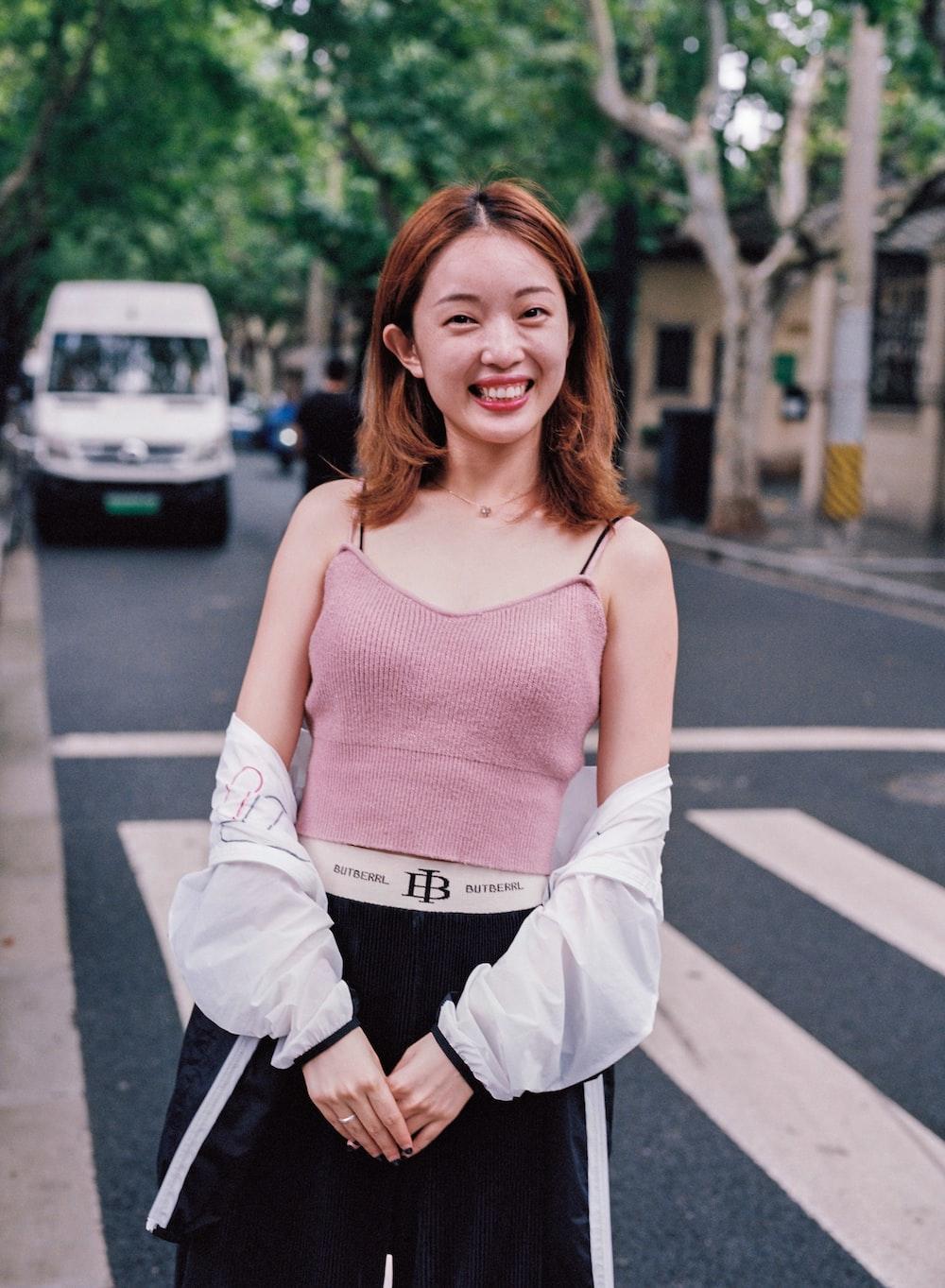 woman in pink top beside pedestrian lane