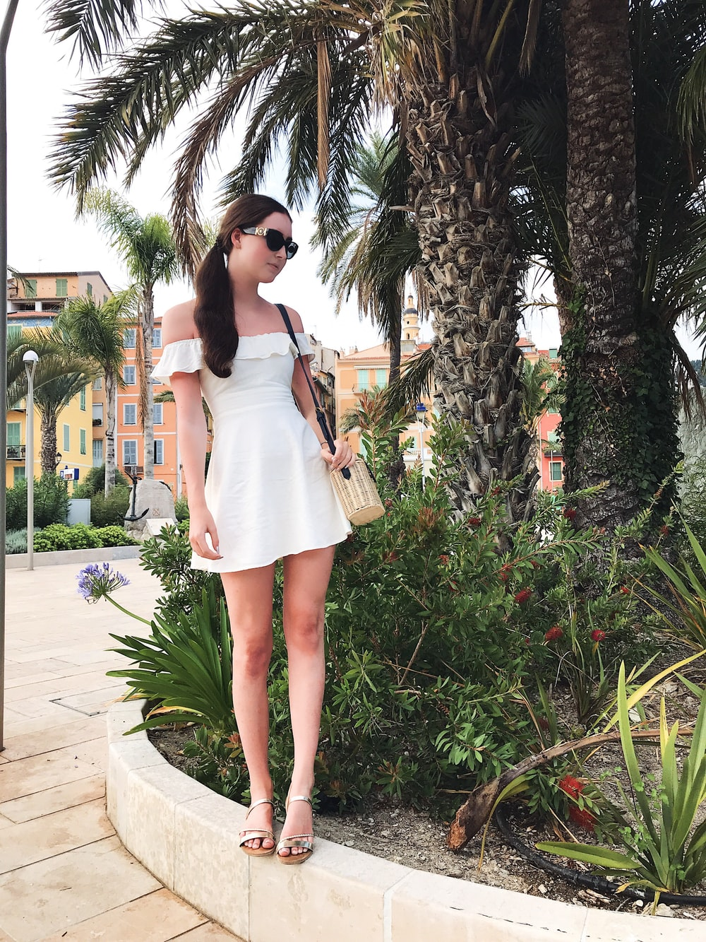 woman in white mini dress beside palm trees