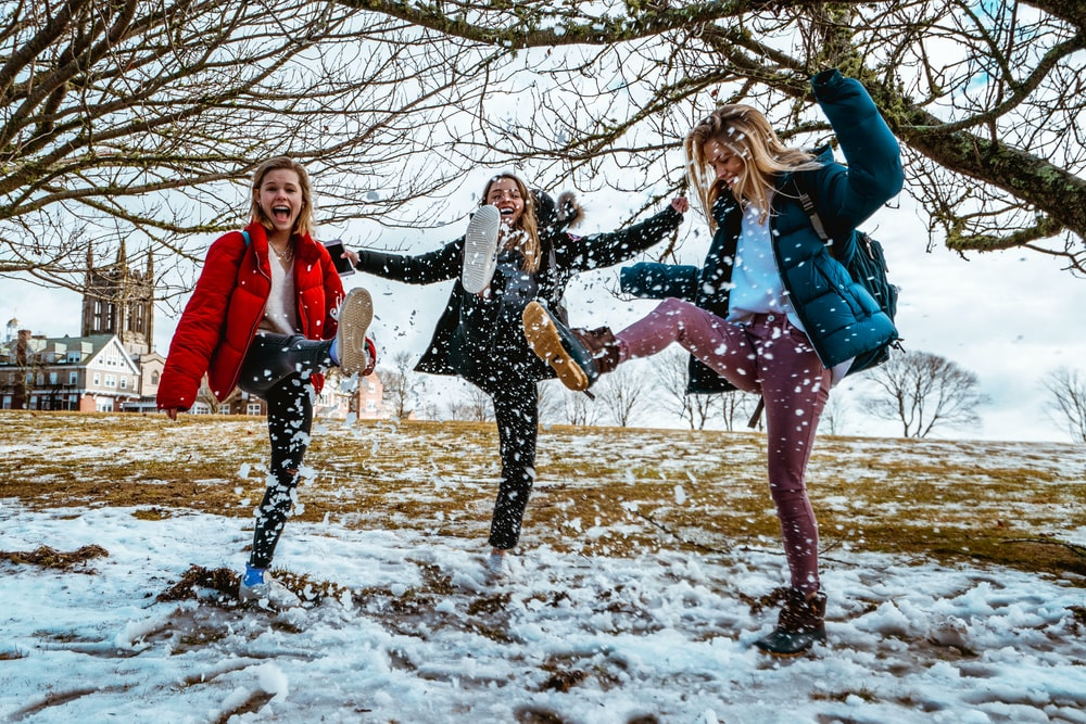 women kicking snow