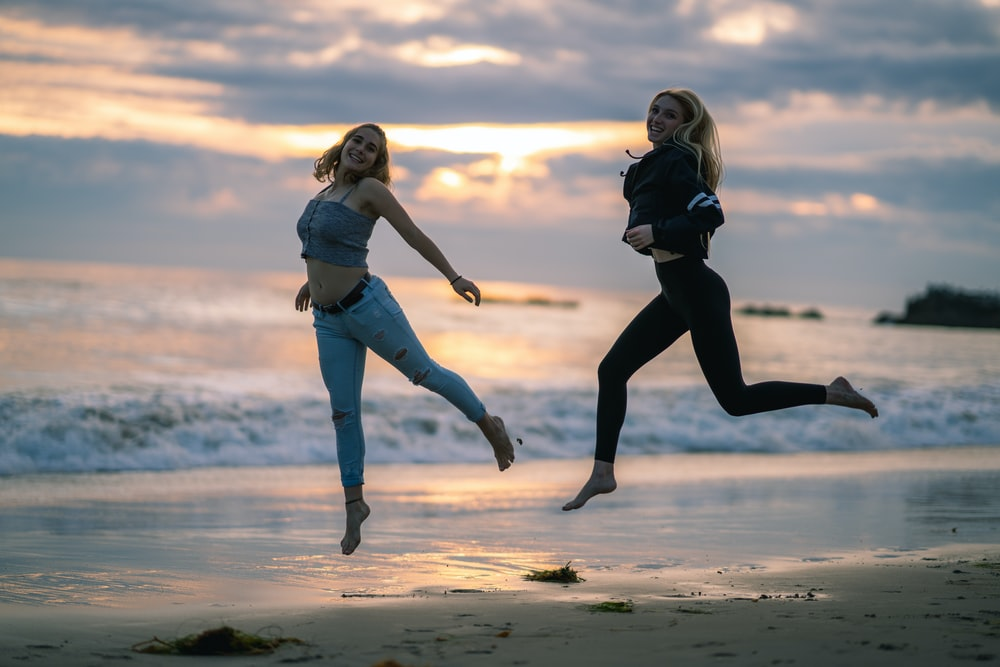 woman wearing blackjacked and black leggings jumping on seashore