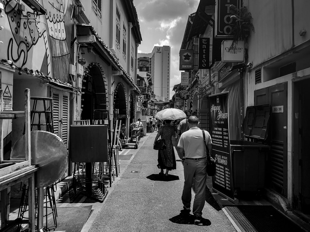 grayscale photography of man and woman walking along narrow pathway