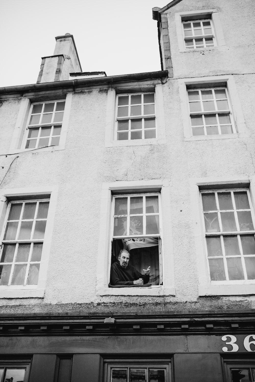 grayscale photo of man on window