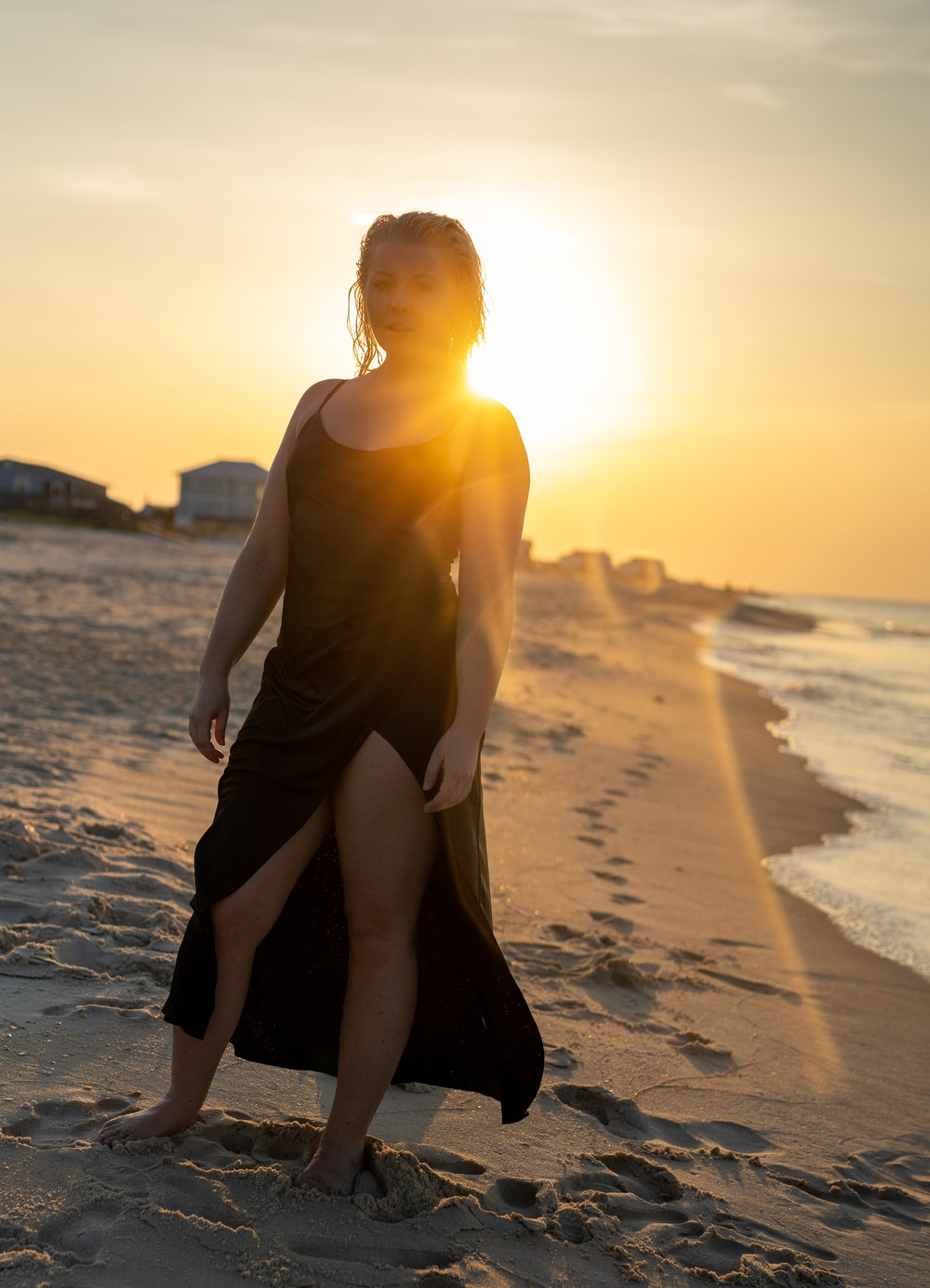woman standing by the seashore during golden hour