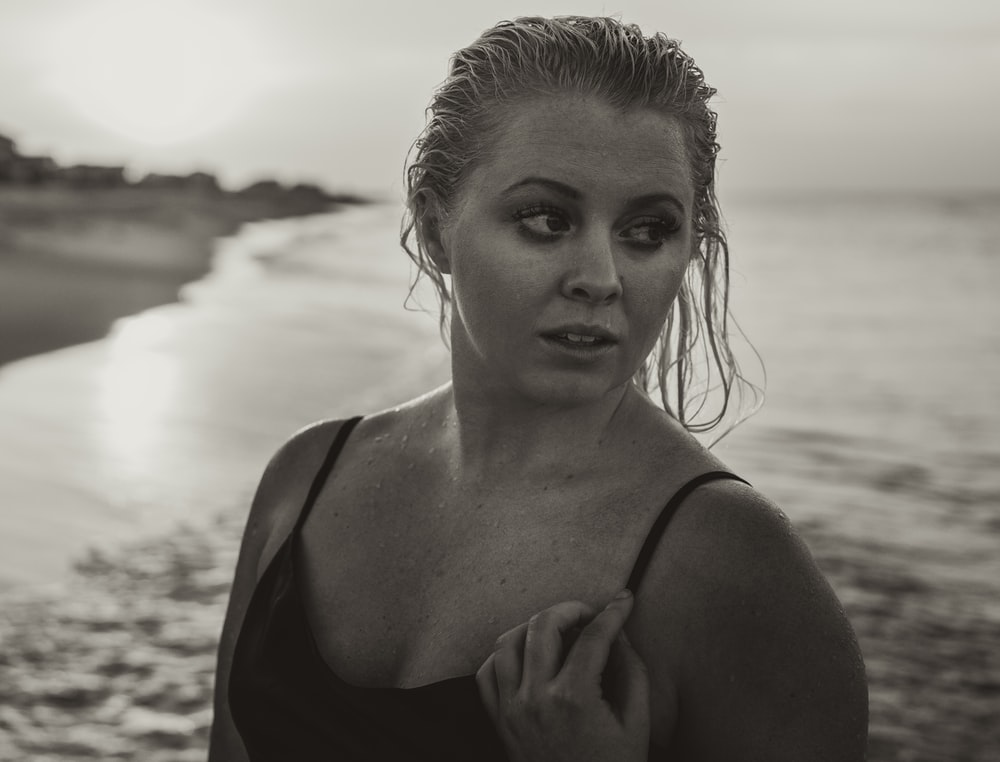 grayscale photography of woman in black top at shore