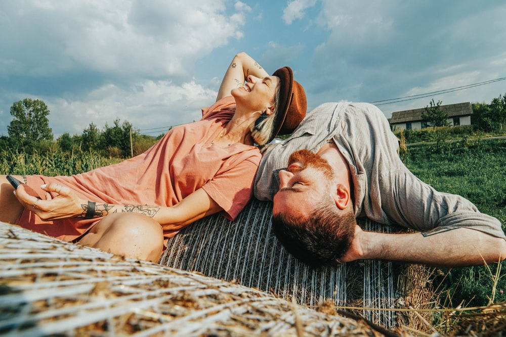 man and woman lying on hay bale during daytime