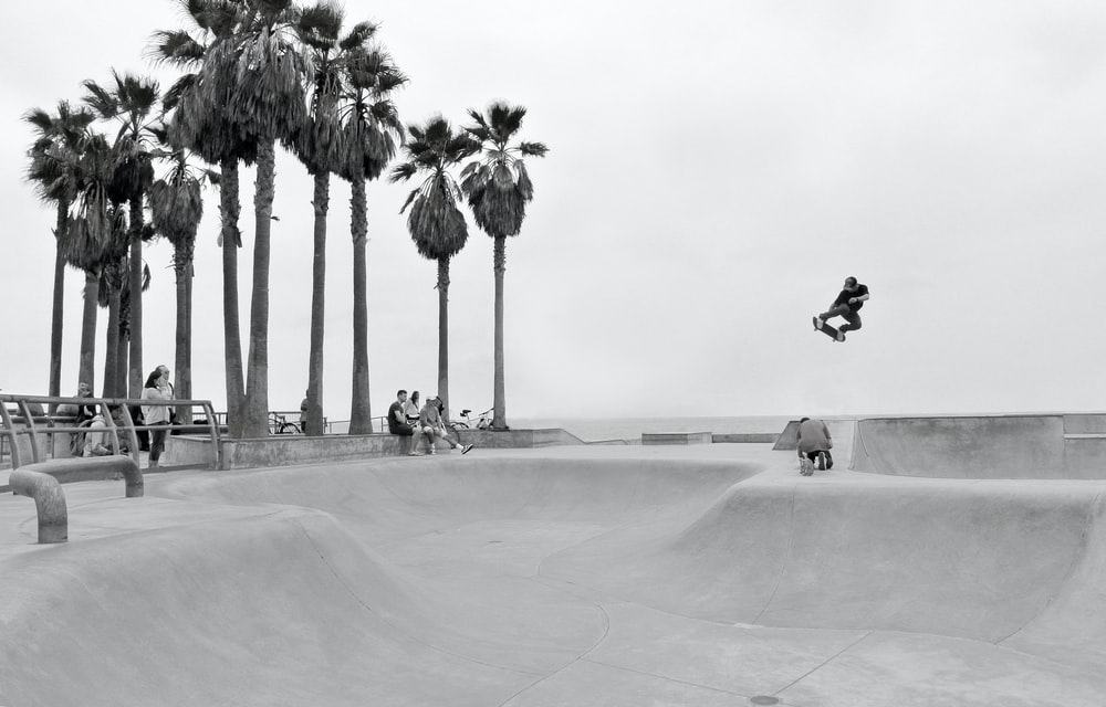 grayscale photography of person skateboarding and people watching