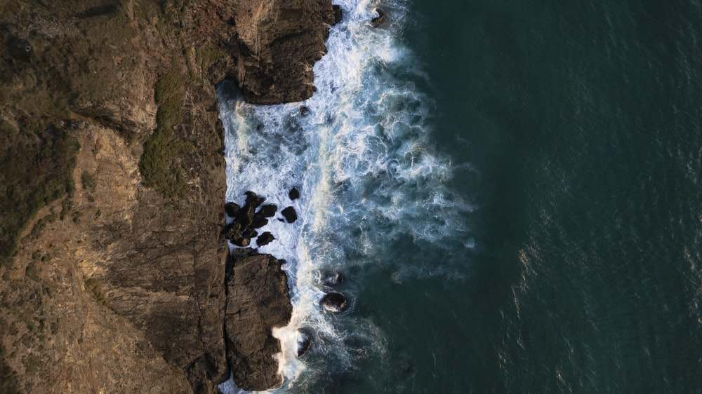 aerial photography of waves crashing on rocks