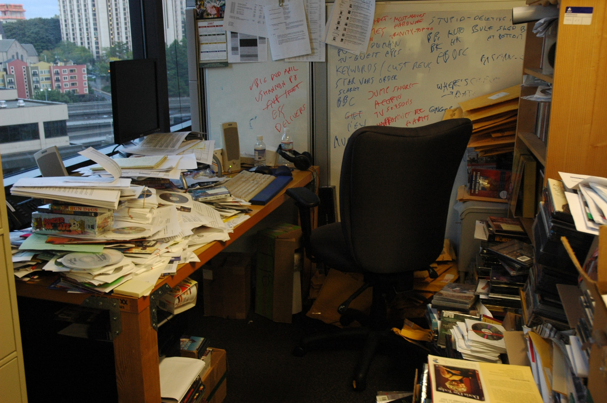 High tech workers office, whiteboard, notes, papers, plans, sample diskettes, stacked, in piles, reviews, keyboard, screen, notes, door desk, speakers, old calendar, cup of noodles, view, high rise, Seattle, Washington, USA