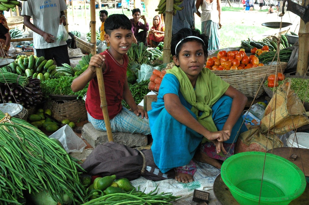 girl and boy sitting between vegetables