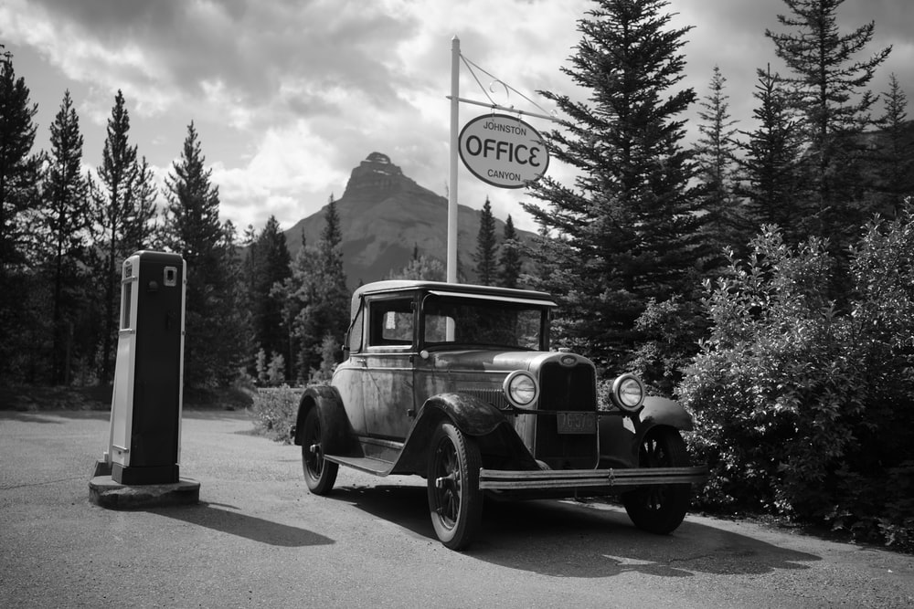 grayscale photo of park vehicle beside trees