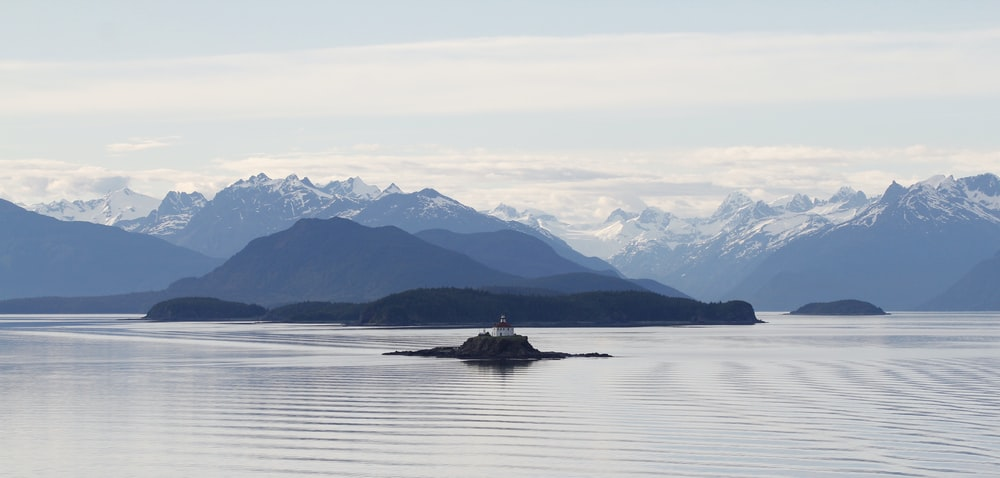 lighthouse on isle near mountains during day
