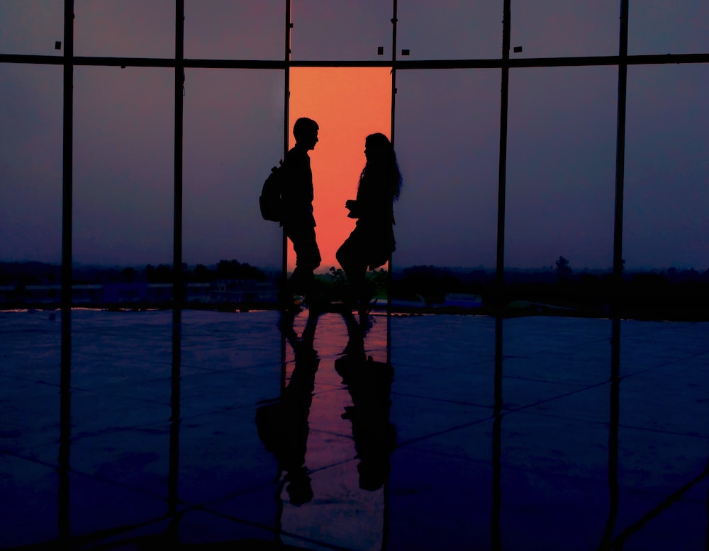 silhouette of man and woman standing inside building
