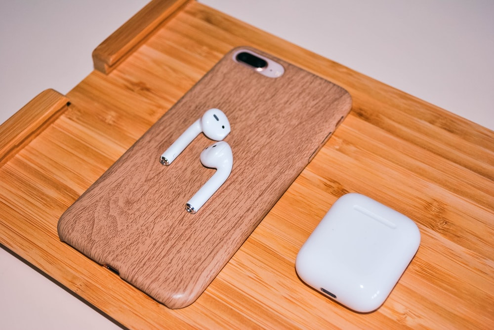 Apple AirPods with charging case on brown chopping board