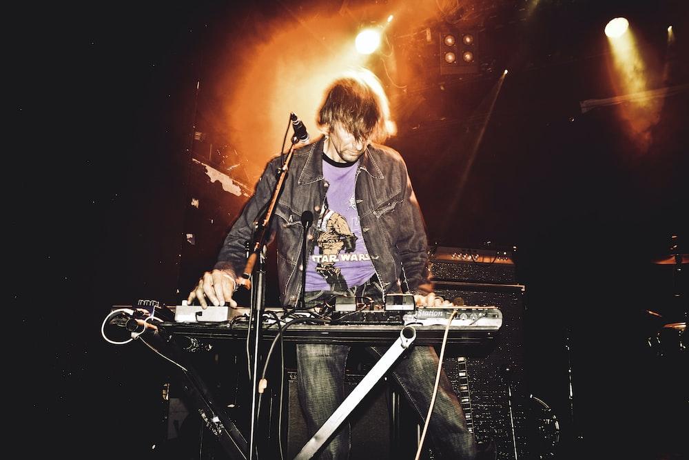 man playing electronic keyboard on stage
