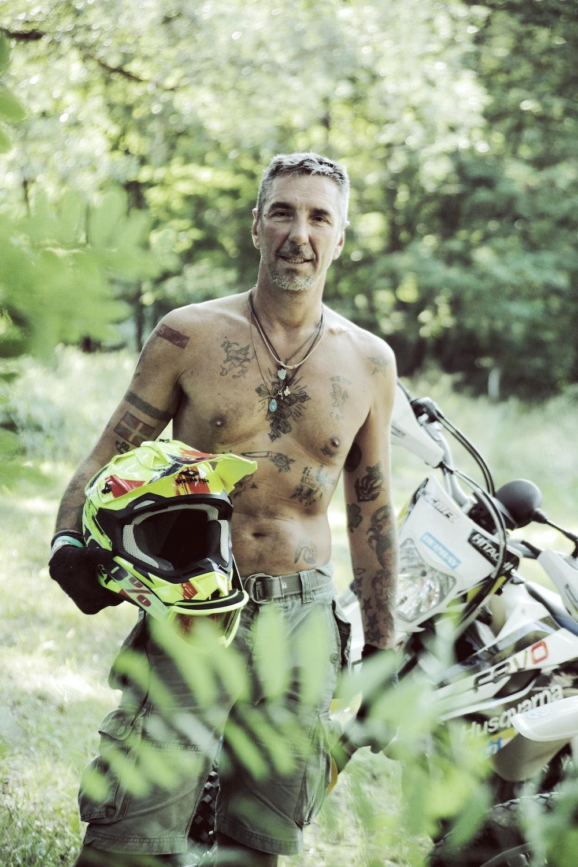 man standing while holding helmet beside dirt bike
