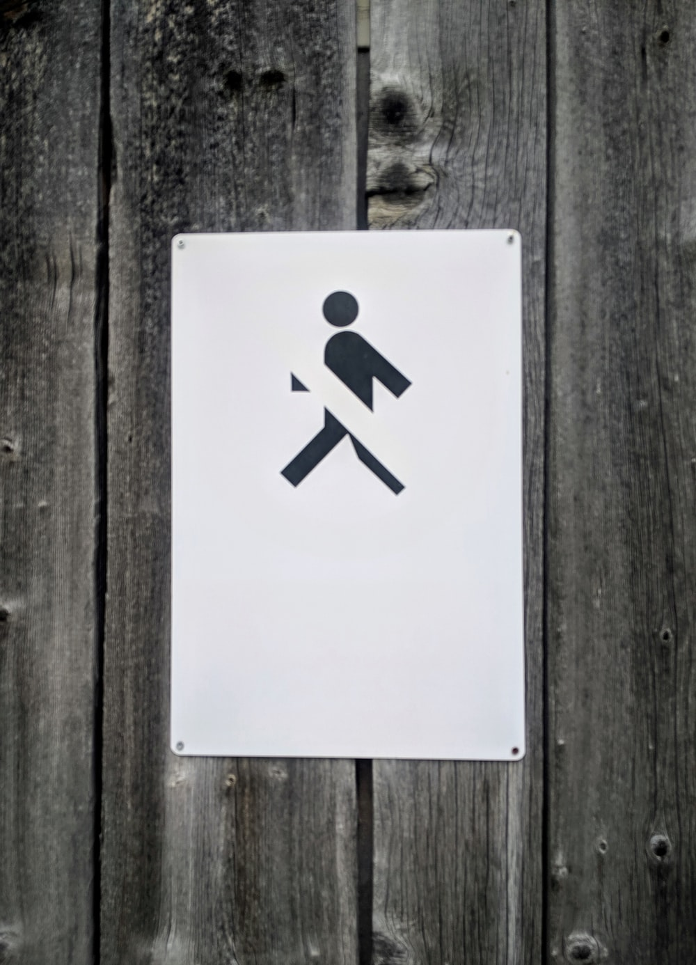 No Walking sign on gray wooden wall