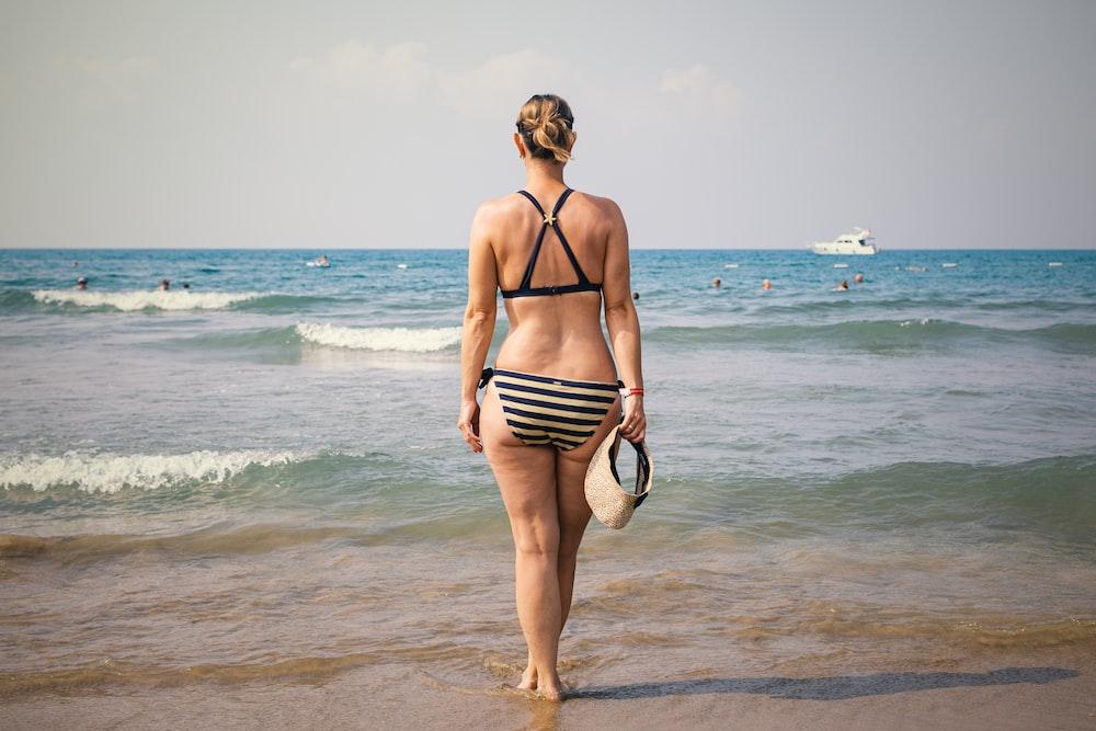 woman holding sunvisor cap wearing striped bikini