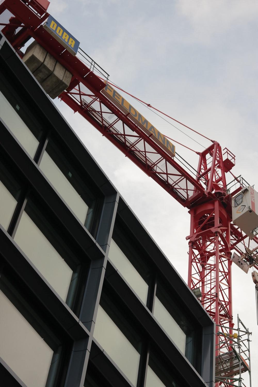red metal crane above gray building