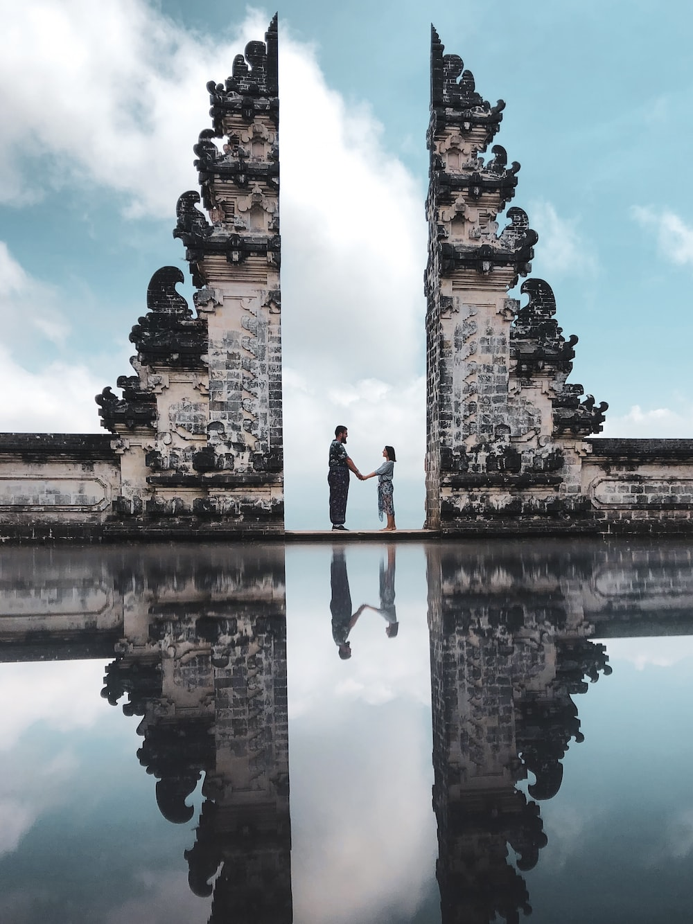 two people standing near calm body of water