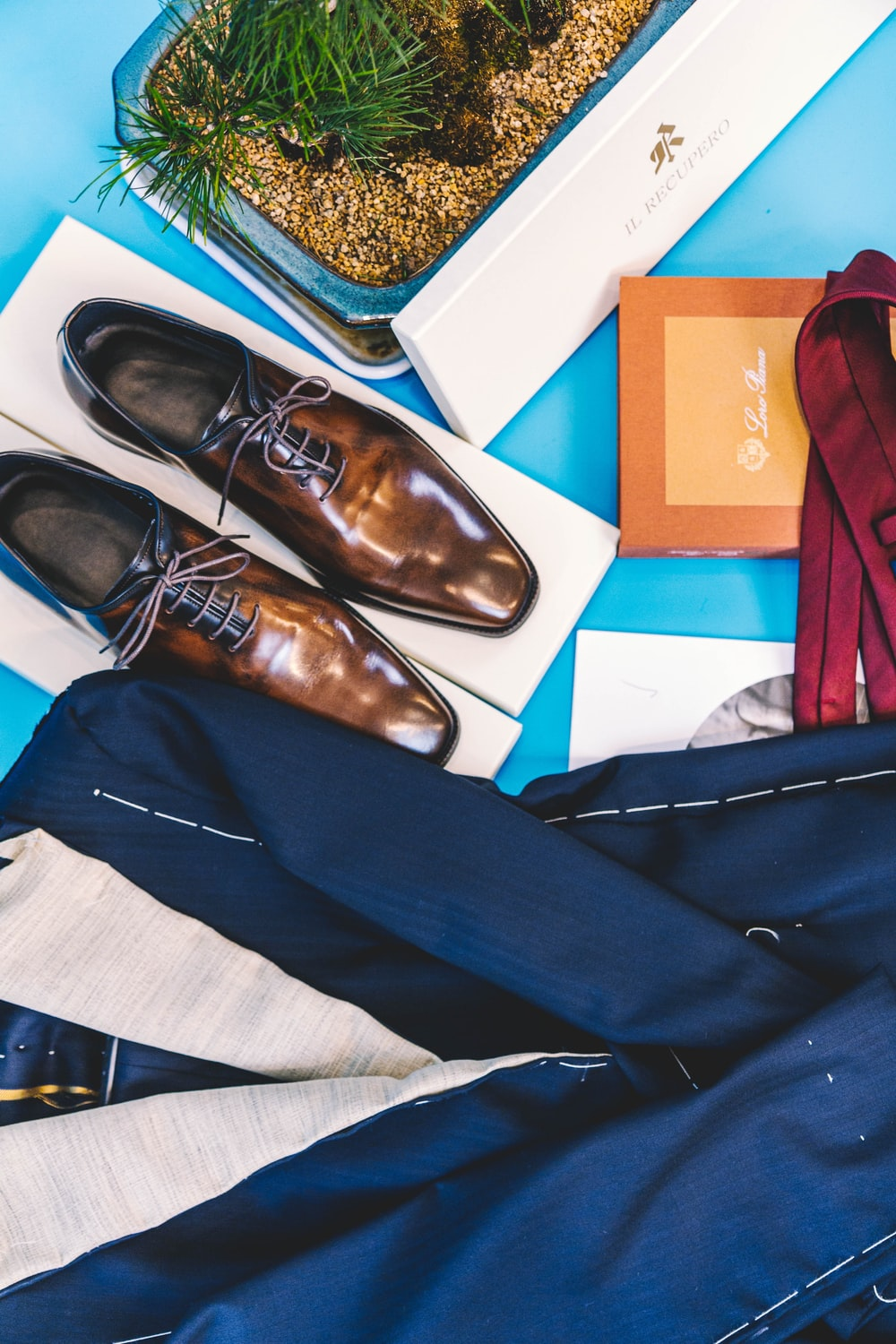 pair of brown leather dress shoes beside blue suit jacket