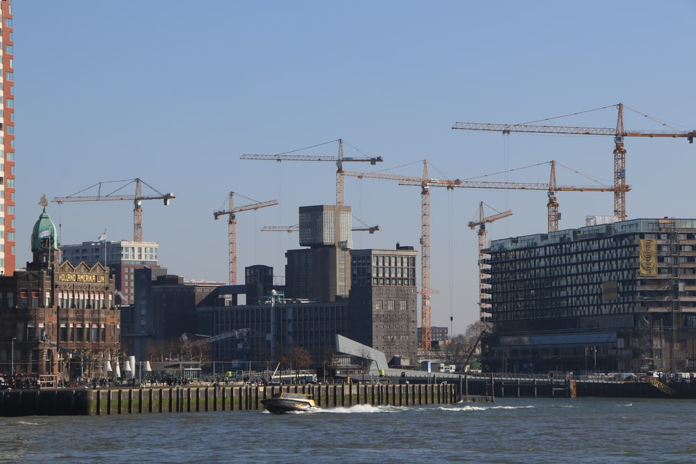 tower cranes beside buildings during daytime