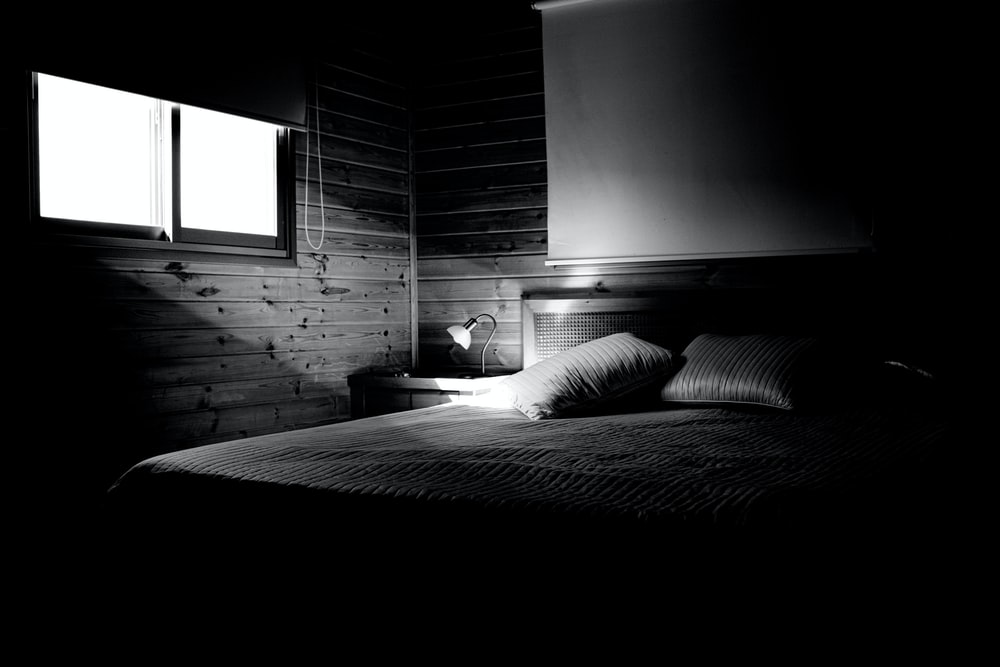 grayscale photography of empty bed
