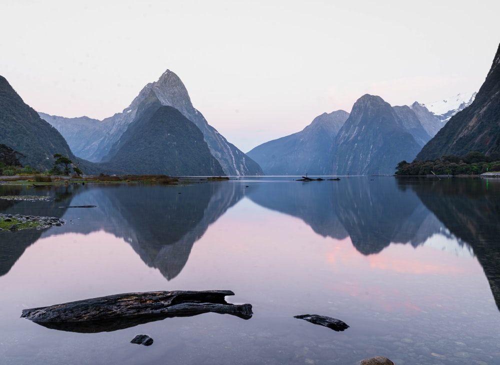 reflection of mountain on body of water during daytime