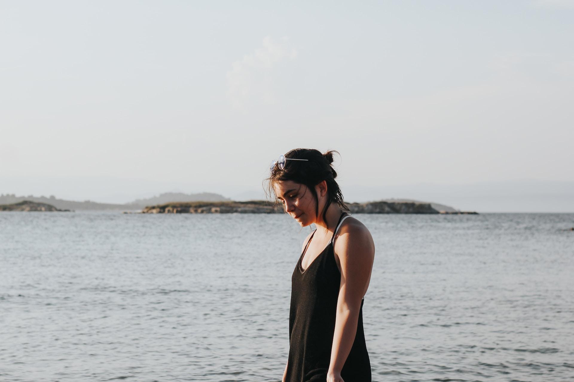 woman wearing black spaghetti strap dress beside beach