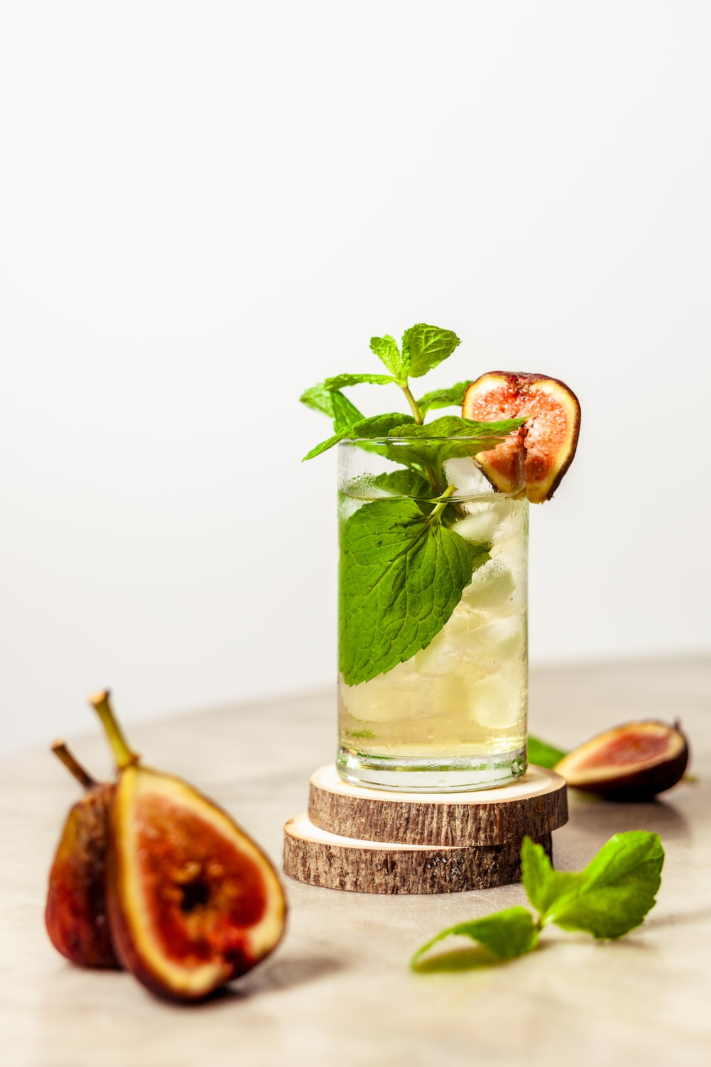 sliced fig fruit near juice with mint on top