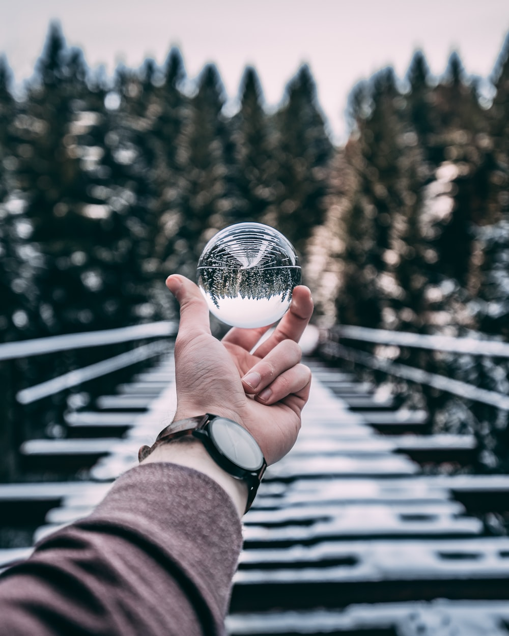 person holding glass ball standing on bridge