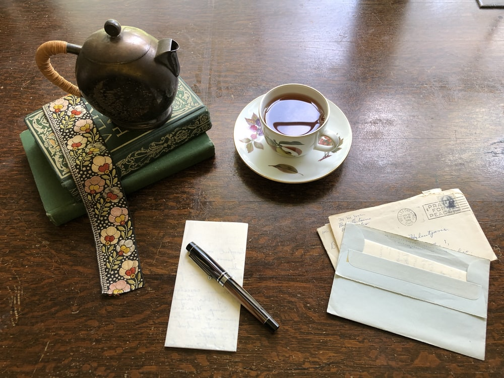 cup of tea beside books and letters