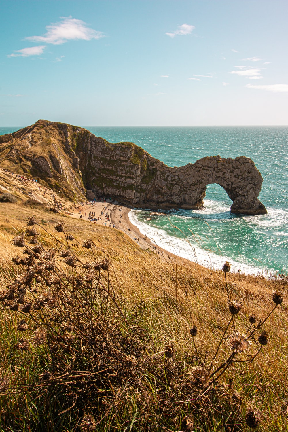 brown sand beach with arch rock