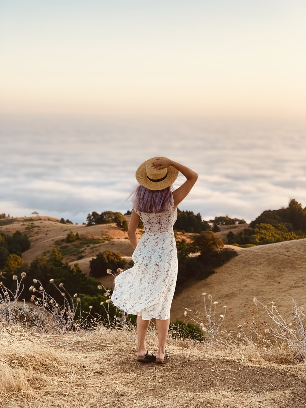 women's white lace dress and brown sunhat on top of hill during daytime